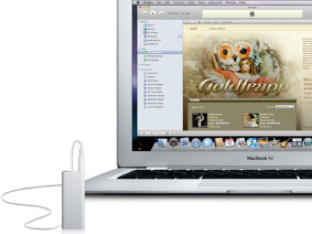 Foto de un Macbook con iTunes corriendo, junto a un iPod.